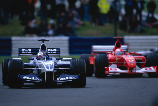 2002 British Grand Prix, Silverstone, England. 7th July 2002. Juan Pablo Montoya leads from Michael Schumacher at the early stages of the Grand Prix.World Copyright - LAT Photographic Ref: 35mm Original A26