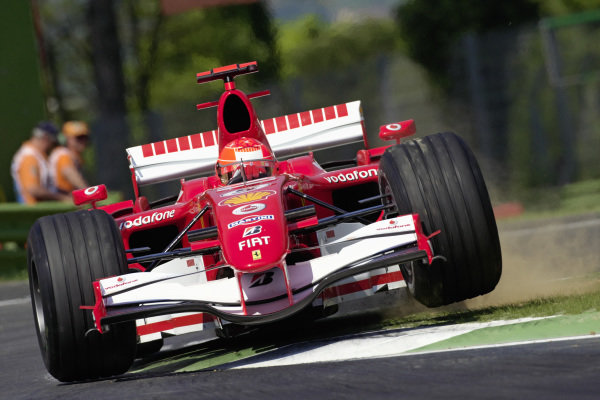 Michael Schumacher, Ferrari 248 F1 cuts the corner, kicking up dust.