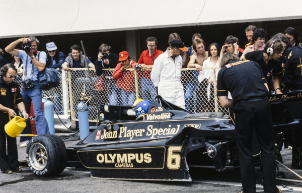 A mechanic cleans off the front tyres of Ronnie Peterson's Lotus 79 Ford in the pitlane.