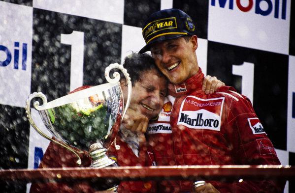 Winner Michael Schumacher celebrates on the podium with Jean Todt.