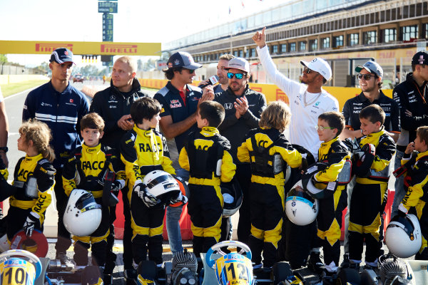 Circuit de Catalunya, Barcelona, Spain. Thursday 11 May 2017. Pascal Wehrlein, Sauber, Valtteri Bottas, Mercedes AMG,Carlos Sainz Jr, Toro Rosso, Lewis Hamilton, Mercedes AMG, and Sergio Perez, Force India, pose for a picture with some young karters. World Copyright: Steve Etherington/LAT Images ref: Digital Image SNE15023