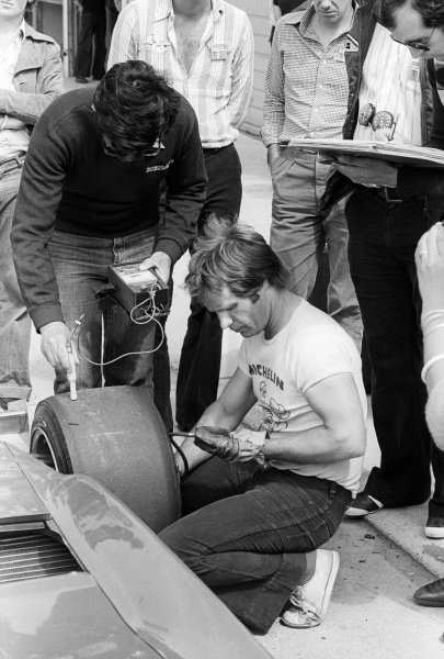 Michelin tyre technicians check the temperature and air pressure of a tyre on a Ferrari 312T3 in the pits.Formula One Testing, Brands Hatch, England, c. June 1978.