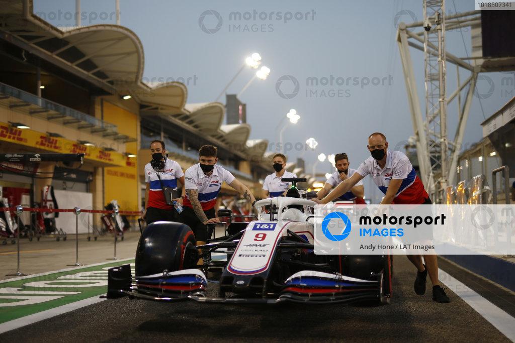 Mechanics push the Nikita Mazepin Haas VF-21 down the pit lane