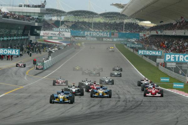 2003 Malaysian Grand Prix. Sepang, Kuala Lumpur, Malaysia.21-23 March 2003.Fernando Alonso (Renault R23) leads into the first corner at the start, followed by Jarno Trulli (Renault R23), David Coulthard (McLaren MP4/17D Mercedes), Michael Schumacher, Rubens Barrichello (both Ferrari F2002's), Kimi Raikkonen (McLaren MP4/17D Mercedes) and Nick Heidfeld (Sauber C22 Petronas). Cristiano da Matta (Toyota TF103) waits in the pit lane.World Copyright - Steve Etherington/LAT Photographic ref: Digital Image Only