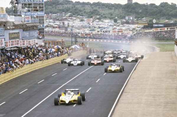 René Arnoux, Renault RE30B, pulls away at the start. Behind is Alain Prost, Renault RE30B, Riccardo Patrese, Brabham BT50 BMW, Gilles Villeneuve, Ferrari 126C2, Carlos Reutemann, Williams FW07D Ford, Didier Pironi, Ferrari 126C2, and Keke Rosberg, Williams FW07D Ford.