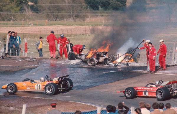1970 Spanish Grand Prix.Jarama, Madrid, Spain.17-19 April 1970.Bruce McLaren (McLaren M14A Ford) and Mario Andretti (March 701 Ford) drive past the flame engulfed cars of Jacky Ickx and Jackie Oliver, after their first lap crash at Bugatti. Oliver's front left stub axle failed and the wheel flew off under braking into the corner, he then crashed straight into the back of ickx's car. Both cars were heavilly fuelled and due to the incompetence of the marshals the fires burned away for more than an hour. They also unsuccessfully tried to remove Oliver's car off the track with a trolley jack. Both drivers escaped serious injury.Ref-70 ESP 02.World Copyright - LAT Photographic