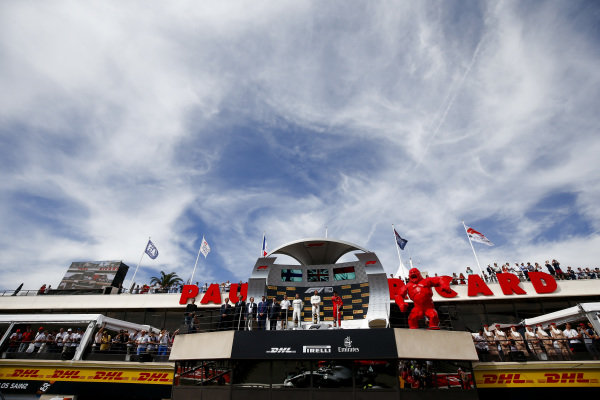 Valtteri Bottas, Mercedes AMG F1, 2nd position, Lewis Hamilton, Mercedes AMG F1, 1st position, and Charles Leclerc, Ferrari, 3rd position, on the podium with their cars parked below