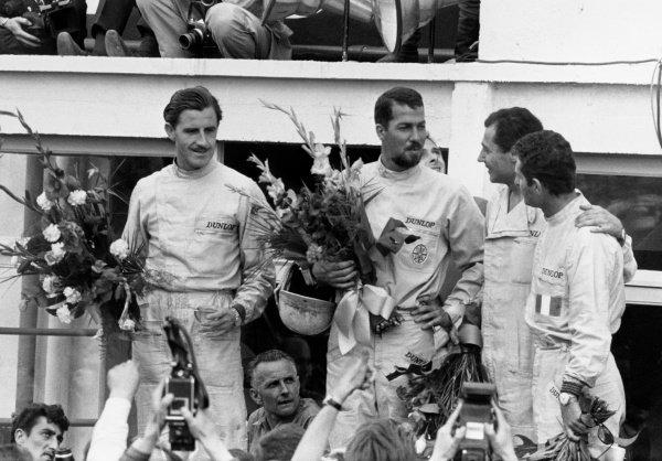 Le Mans, France. 20th - 21st June 1964.Jo Bonnier/Graham Hill (Ferrari 330P-64), 2nd position,on the podium with Jean Guichet/Nino Vaccarella (Ferrari 275P), 1st position, portrait.World Copyright: LAT Photographic .Ref: B/W Print.
