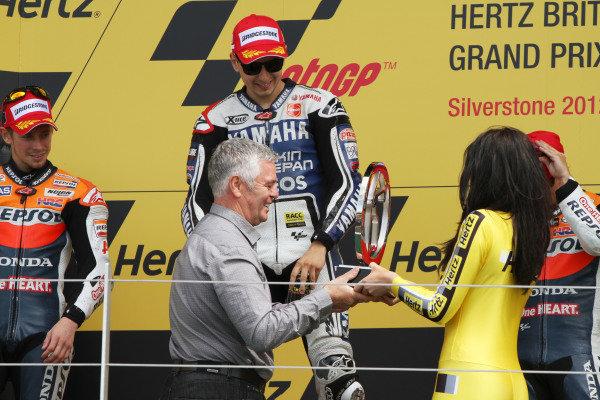 British Grand Prix.  Silverstone, England. 15th-17th June 2012.  Jorge Lorenzo, Yamaha, receives the winner's trophy from Derek Warwick.  World Copyright: Kevin Wood/LAT Photographic.  ref: Digital Image IMG_8606a