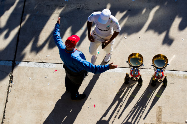 Circuit of the Americas, Austin, Texas, United States of America. Sunday 22 October 2017. Niki Lauda, Non-Executive Chairman, Mercedes AMG, embraces Lewis Hamilton, Mercedes AMG, 1st Position, alongside the winning driver and constructor trophies. World Copyright: Sam Bloxham/LAT Images  ref: Digital Image _W6I8536