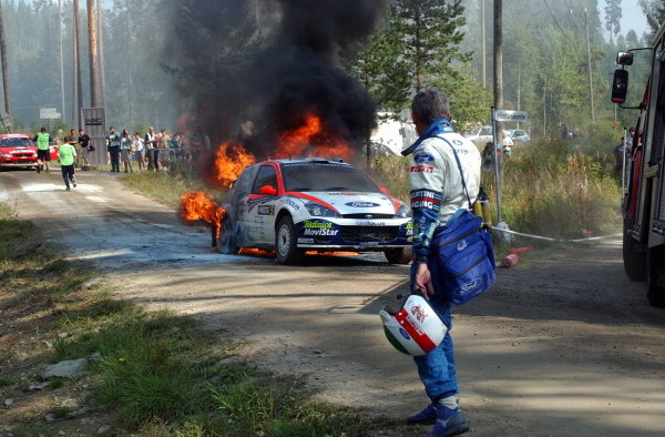 Co-driver Nicky Grist (GBR) watches the Ford Focus RS WRC burn after a loose hyrdaulic cable caught fire.