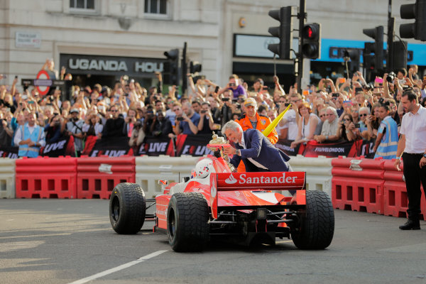 London, United Kingdom.  Wednesday 12 July 2017. Jenson Button, McLaren, gives a passenger ride to Naomi Campbell in the 2 seater and Damon Hill offers the British Grand Prix trophy as a joke. World Copyright: Zak Mauger/LAT Images  ref: Digital Image _54I2710