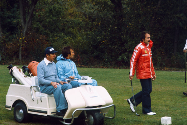 Watkins Glen, New York, USA. 3-5 October 1975. Rob Walker and Carlos Reutemann sit in their buggie and watch Clay Regazzoni play golf before the race, portrait.  World Copyright: LAT Photographic. Ref: 75USA04.