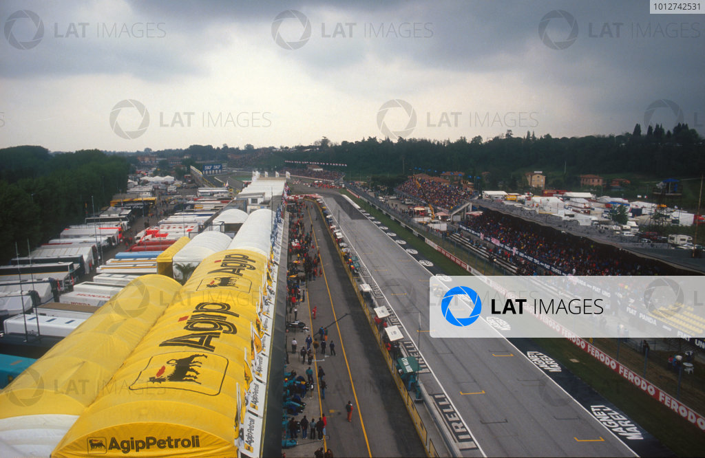 1991 San Marino Grand Prix.Imola, Italy.26-28 April 1991.Pierluigi Martini (Minardi M191 Ferrari) 4th position, drives by the grandstands and the pits on the start/finish straight with dark skies looming.Ref-91 SM 23.World Copyright - LAT Photographic