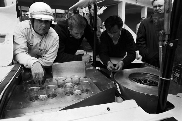 Phil Hill studies the engine bay and wing struts of his Chaparral Cars Inc, Chaparral 2F Chevrolet 2F002 CZV-659 before the start.