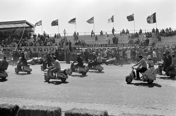 Fans parade on their scooters in front of the pits, before the race.