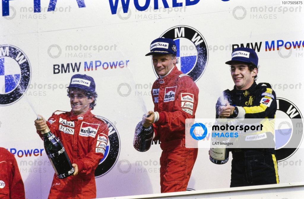 Niki Lauda, 1st position, celebrates his final grand prix win alongside Alain Prost, 2nd position, and Ayrton Senna, 3rd position, on the podium.
