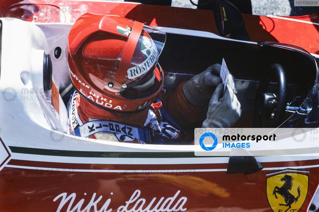 Niki Lauda sits in his cockpit examining data.