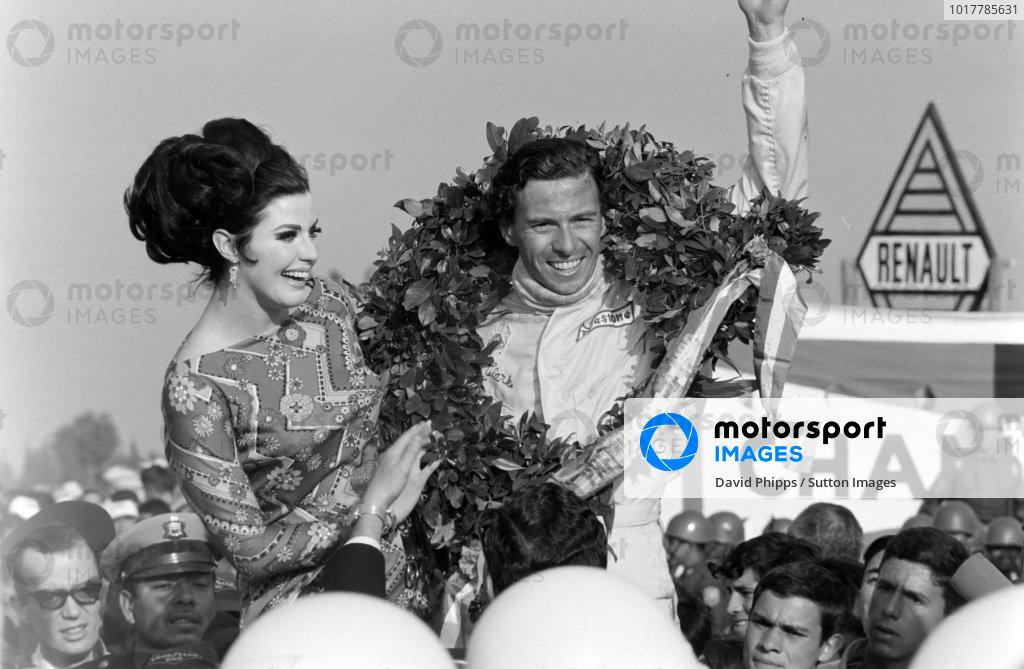 Jim Clark, 1st position, celebrates victory on the podium.
