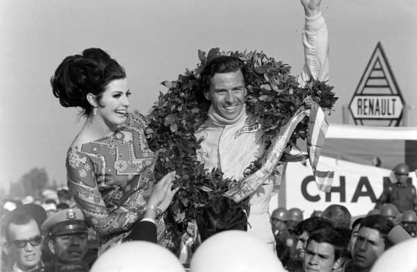 Jim Clark, 1st position, celebrates victory on the podium.
