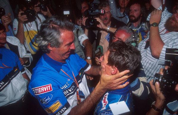 1994 Australian Grand Prix.Adelaide, Australia.11-13 November 1994.Benetton team boss Flavio Briatore congratulates his driver Michael Schumacher on becoming the new drivers World Champion.Ref-94 AUS 15.World Copyright - LAT Photographic