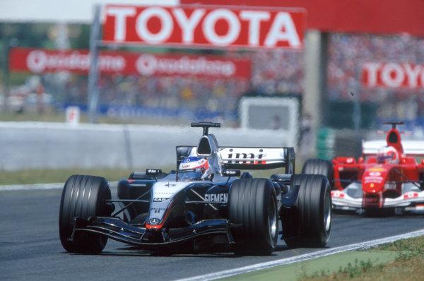 2004 French Grand PrixMagny-Cours, France. 2nd - 4th JulyKimi Raikkonen, McLaren Mercedes MP4/19 leads Rubens Barrichello, Ferrari F2004. Action. World Copyright: LAT PhotographicRef:35mm Image A14