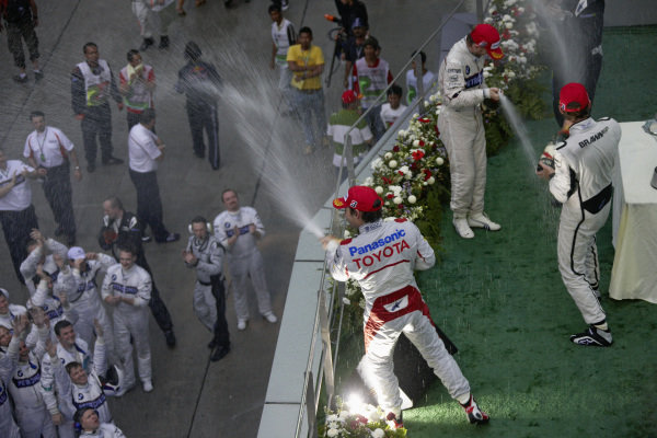 Nick Heidfeld, 2nd position, winner Jenson Button, and Timo Glock, 3rd position celebrate with champagne on the podium.