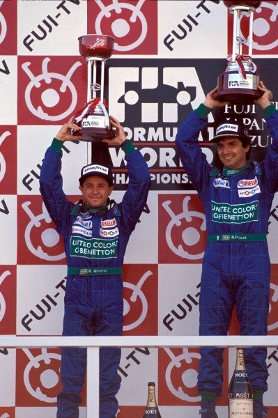 Roberto Moreno and Nelson Piquet with their trophies on the podium.