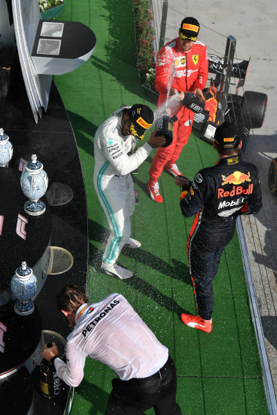 Lewis Hamilton, Mercedes AMG F1, 1st position, Max Verstappen, Red Bull Racing, 2nd position, and Sebastian Vettel, Ferrari, 3rd position, celebrate on the podium with Champagne