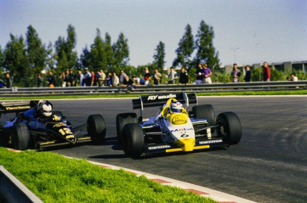 Keke Rosberg, Williams FW09B Honda, sliding, leads Nigel Mansell, Lotus 95T Renault.