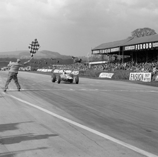 Jim Clark, Lotus 25 Climax takes the chequered flag for victory.