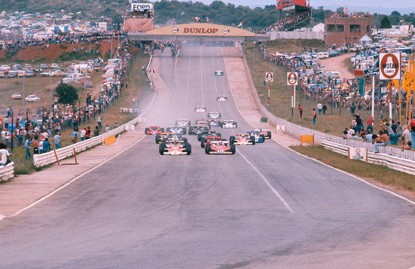 1977 South African Grand Prix.Kyalami, South Africa.3-5 March 1977.James Hunt (McLaren M23 Ford) and Niki Lauda (Ferrari 312T2) lead the field down to Turn 1 at the start.Ref-77 SA 12.World Copyright - LAT Photographic