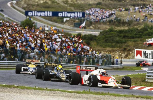 Alain Prost, McLaren MP4-2C TAG, leads Ayrton Senna, Lotus 98T Renault, and Nelson Piquet, Williams FW11 Honda.