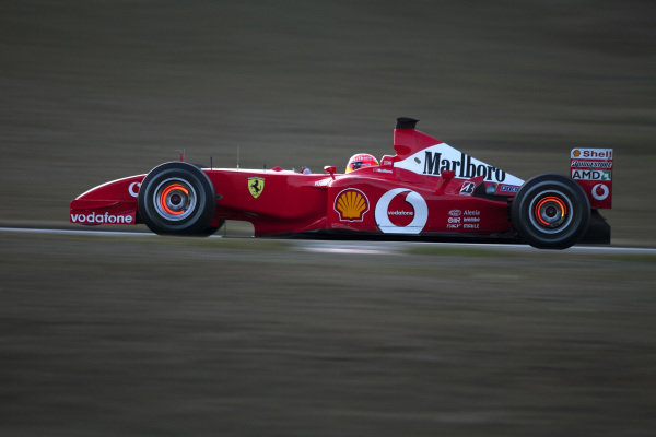 Michael Schumacher drives the new Ferrari F2002, with brake discs glowing.