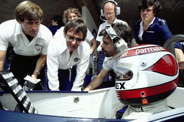 Nelson Piquet, Brabham BT49C Ford, studies lap times along with Bernie Ecclestone and Gordon Murray in the pits.