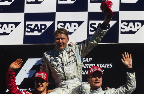 Mika Häkkinen, 1st position, Michael Schumacher, 2nd position, and David Coulthard, 3rd position, celebrate on the podium.