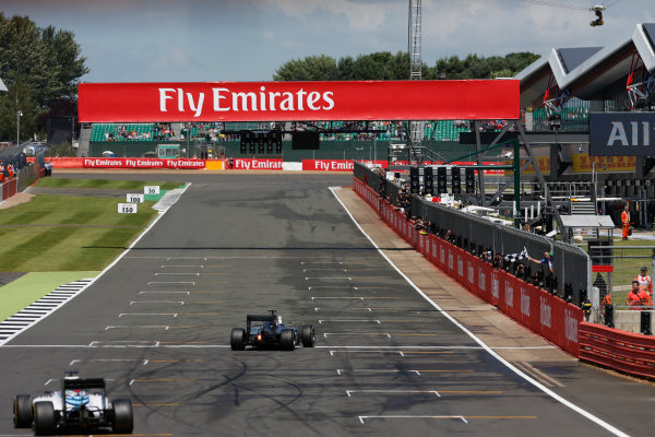 2016 British Grand Prix. Silverstone, Northamptonshire, UK. Sunday 10 July 2016. Lewis Hamilton, Mercedes F1 W07 Hybrid punches the air as he crosses the finish and takes the chequered flag. World Copyright: Ferraro/LAT Photographic ref: Digital Image _40I5018
