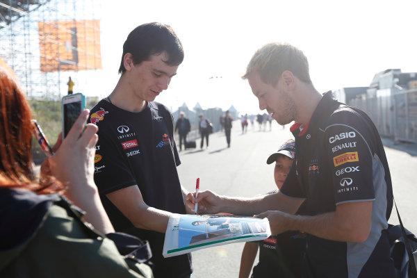 Korea International Circuit, Yeongam-Gun, South Korea. Saturday 5th October 2013. Sebastian Vettel, Red Bull RB9 Renault, signs an autograph for a fan. World Copyright: Andrew Ferraro/LAT Photographic. ref: Digital Image _79P1202