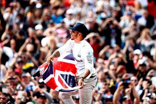 Silverstone, Northamptonshire, UK Sunday 10 July 2016. Lewis Hamilton, Mercedes AMG, 1st Position, celebrates victory at his home race with a Union flag and the fans. World Copyright: Dunbar/LAT Photographic ref: Digital Image _V2I1665