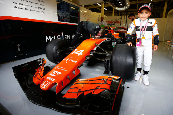 Silverstone, Northamptonshire, UK.  Sunday 16 July 2017. A young fan stands next to the Fernando Alonso McLaren MCL32 Honda.  World Copyright: Andy Hone/LAT Images  ref: Digital Image _ONZ6686