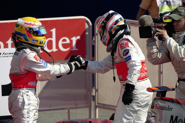 Teammates Lewis Hamilton and Fernando Alonso shake hands in parc fermé after claiming a 1-2 victory.