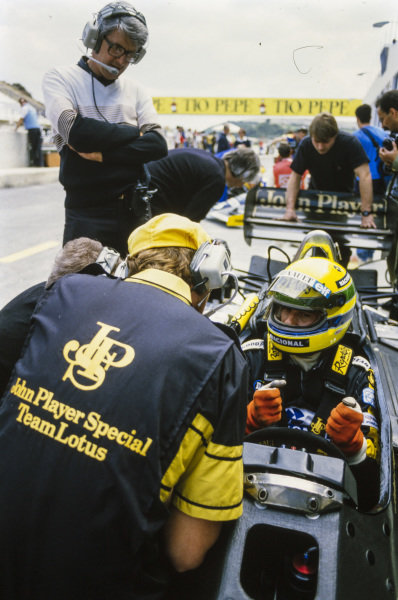 Ayrton Senna, Lotus 98T Renault, in conversation in the pits. Peter Warr stands behind the cockpit.