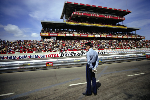 A French policeman guards the pitlane entry opposite the main grandstand.