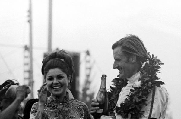 Race winner and World Champion for the second time Graham Hill (GBR) Lotus enjoys a champagne moment with the girl beside him on the podium. Mexican Grand Prix, Mexico City, 3 November 1968.