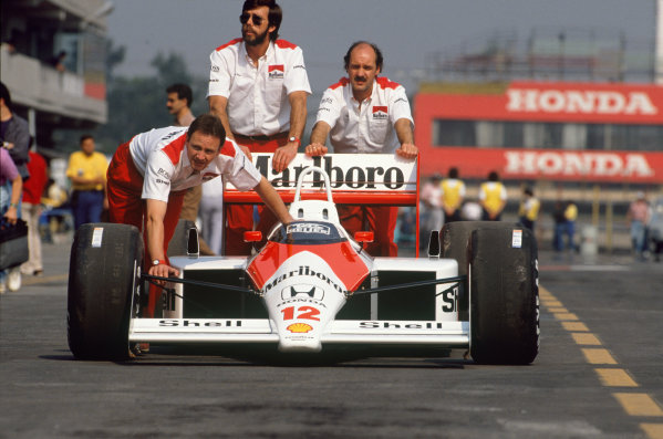 Mexico City, Mexico. 27th - 29th May 1988.Mechanics push Ayrton Senna's McLaren MP4/4 Honda through the pit lane, portrait. World Copyright: LAT Photographic.Ref: 88MEX14