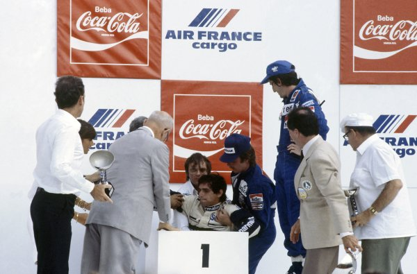 1982 Brazilian Grand Prix.Rio de Janeiro, Brazil. 19-21 March 1982.Nelson Piquet (Brabham BT49D-Ford Cosworth) collapses on the podium through heat exhaustion. Team owner Bernie Ecclestone and Keke Rosberg (Williams FW07C-Ford Cosworth) help while Alain Prost (Renault RE30B) looks on. Piquet and Rosberg were subsequently disqualified for having underweight cas, promoting Prost to 1st position.World Copyright: LAT PhotographicRef: 35mm transparency 82BRA32
