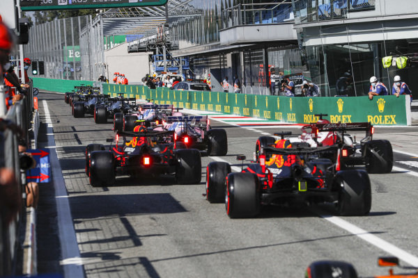 Alexander Albon, Red Bull Racing RB16, Kimi Raikkonen, Alfa Romeo Racing C39, and Max Verstappen, Red Bull Racing RB16, head out of the pits behind the queue