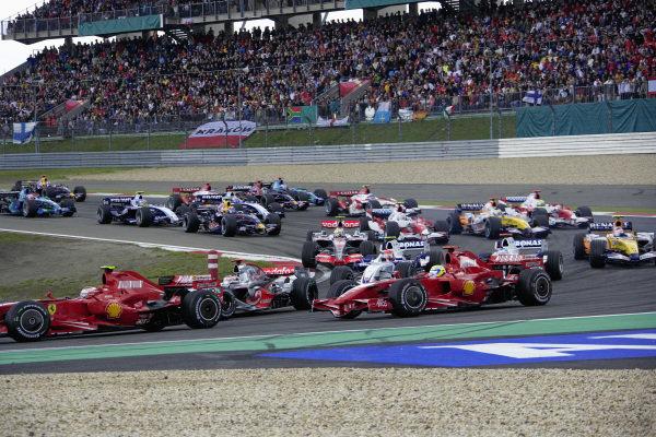 Kimi Räikkönen, Ferrari F2007 leads Fernando Alonso, McLaren MP4-22 Mercedes and Felipe Massa, Ferrari F2007 around the first corner at the start.