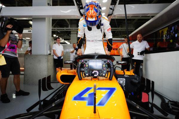 Lando Norris, McLaren MCL33, climbs into the car in the garage