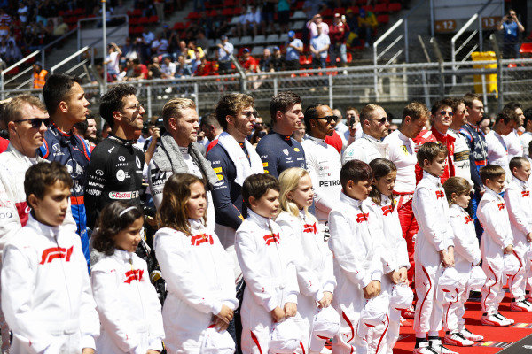 The drivers line up with the grid kids for the national anthem prior to the start